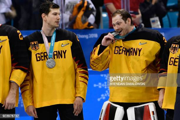 TOPSHOT Germany's Danny aus den Birken bites his silver medal on the podium during the medal ceremony after the men's gold medal ice hockey match...