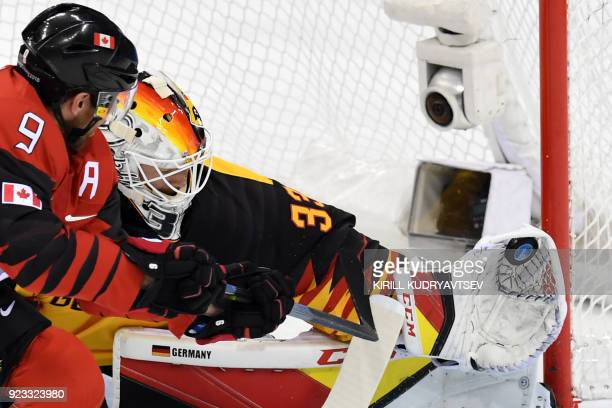 Germany's Danny aus den Birken makes a save against Canada's Derek Roy in the men's semifinal ice hockey match between Canada and Germany during the...