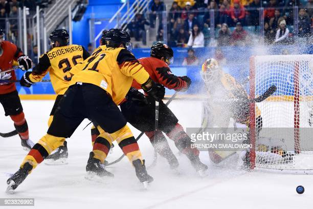 TOPSHOT Germany's Danny aus den Birken makes a save past Canada's Wojciech Wolski in the men's semifinal ice hockey match between Canada and Germany...