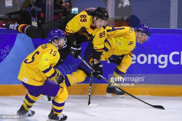 TOPSHOT Germany's David Wolf and Sweden's Staffan Kronwall fight for the puck as Sweden's Simon Bertilsson looks on in the men's quarterfinal ice...