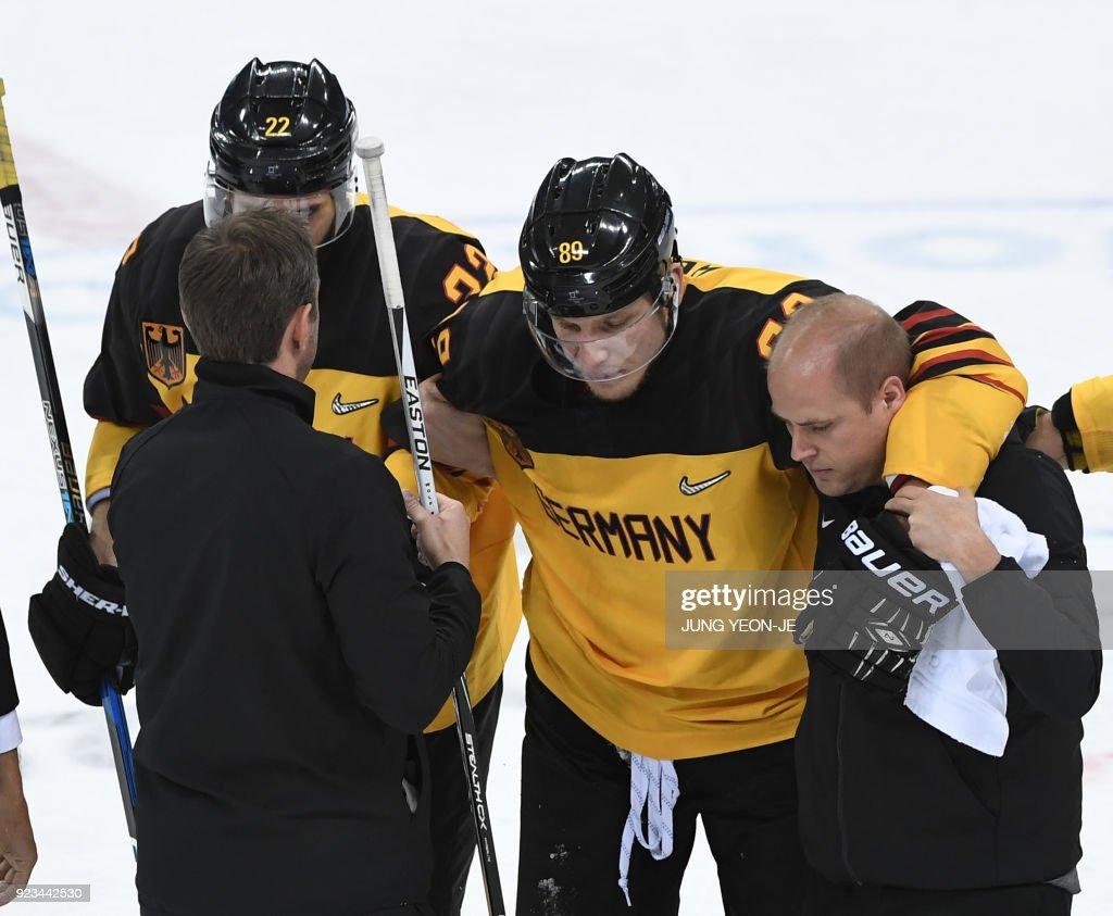 TOPSHOT - Germany's David Wolf is helped off the ice after being injured in the men's semi-final ice hockey match between Canada and Germany during the Pyeongchang 2018 Winter Olympic Games at the Gangneung Hockey Centre in Gangneung on February 23, 2018. / AFP PHOTO / JUNG Yeon-Je