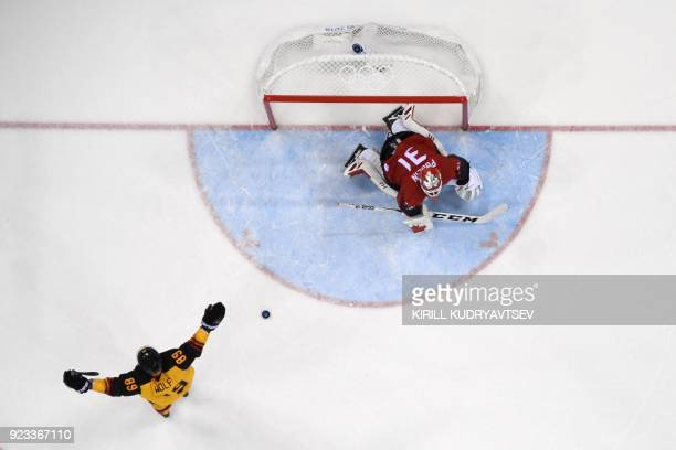 TOPSHOT Germany's David Wolf reacts after teammate Frank Mauer scored against Canada's Kevin Poulin in the men's semifinal ice hockey match between...