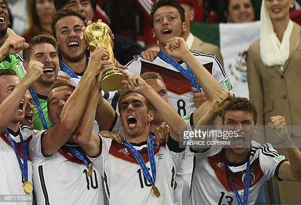 Germany's defender and captain Philipp Lahm and teammates celebrate with the World Cup trophy after they won the 2014 FIFA World Cup final football...