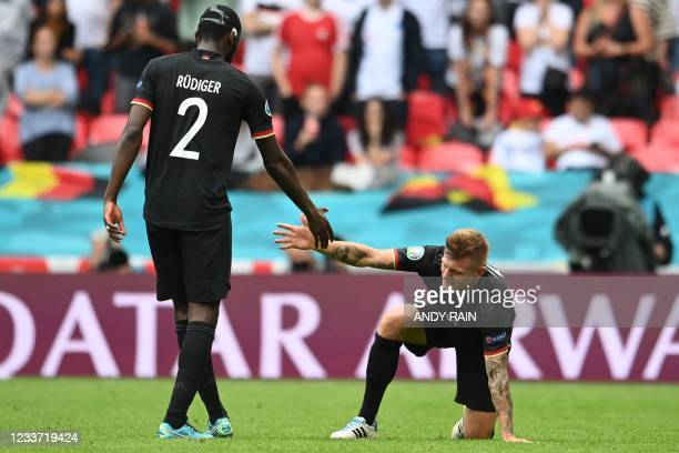 Germany's defender Antonio Ruediger helps Germany's midfielder Toni Kroos back to his feet during the UEFA EURO 2020 round of 16 football match...