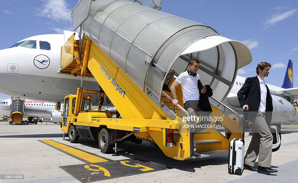 Germany's defender Arne Friedrich (R) and Germany's striker Lukas Podolski (L) get off the plane in Verona May 21, 2010, as the German team arrives for a 12-day long training camp near Bolzano to prepare for the upcoming FIFA Football World Cup in South Africa.