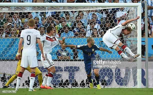 Germany's defender Benedikt Hoewedes heads the ball towards the goal as Argentina's midfielder Javier Mascherano and Germany's forward Miroslav Klose...