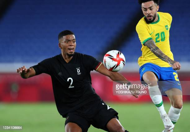 Germany's defender Benjamin Henrichs and Brazil's midfielder Claudinho go for the ball during the Tokyo 2020 Olympic Games men's group D first round...