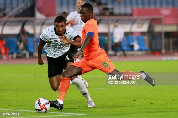 Germany's defender Felix Uduokhai fights for the ball with Ivory Coast's forward Max Gradel during the Tokyo 2020 Olympic Games men's group D first...