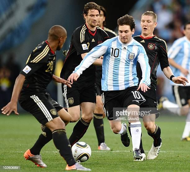 Germany's defender Jerome Boateng defender Arne Friedrich and midfielder Bastian Schweinsteiger close around Argentina's striker Lionel Messi during...