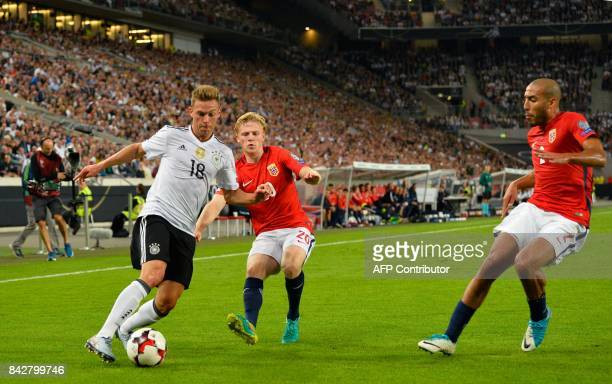Germany's defender Joshua Kimmich vies with Norway's midfielder Mats Moeller Daehli as Norway's defender Haitam Aleesami R looks on during the FIFA...