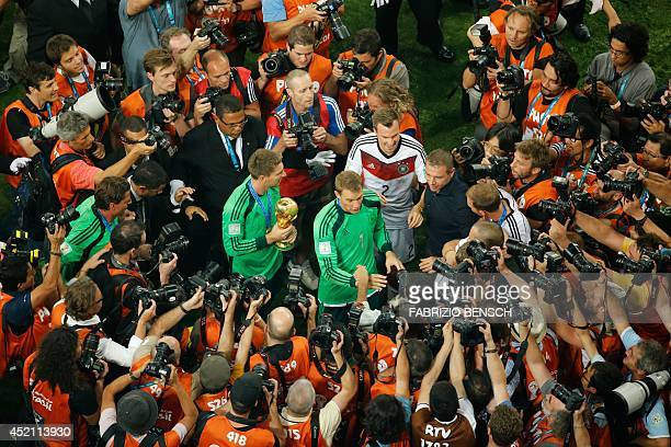 Germany's defender Kevin Grosskreutz and Germany's goalkeeper Manuel Neuer are surrounded by photographers as they celebrate victory in the final...