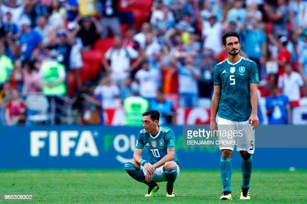TOPSHOT Germany's defender Mats Hummels and Germany's midfielder Mesut Ozil react to their defeat during the Russia 2018 World Cup Group F football...