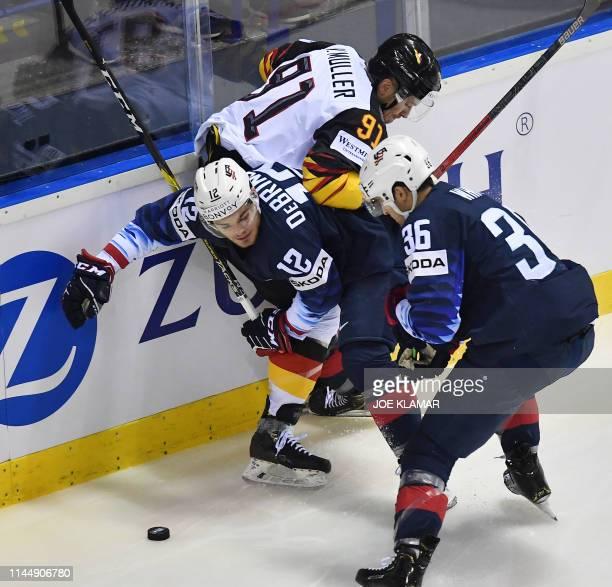 Germany's defender Moritz Muller US' forward Alex Debrincat and US' forward Colin White vie during the IIHF Men's Ice Hockey World Championships...