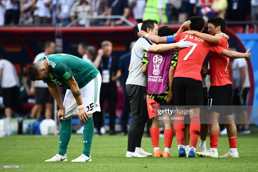 TOPSHOT - Germany's defender Niklas Suele (L) reacts next to South Korea's team players celebrating at the end of the Russia 2018 World Cup Group F football match between South Korea and Germany at the Kazan Arena in Kazan on June 27, 2018. (Photo by Jewel SAMAD / AFP) / RESTRICTED