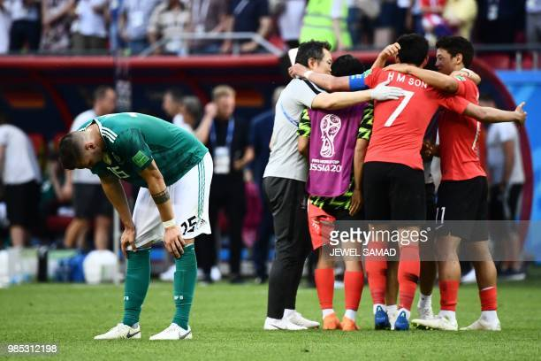 TOPSHOT Germany's defender Niklas Suele reacts next to South Korea's team players celebrating at the end of the Russia 2018 World Cup Group F...