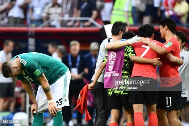 Germany's defender Niklas Suele reacts next to South Korea's team players celebrating at the end of the Russia 2018 World Cup Group F football match...