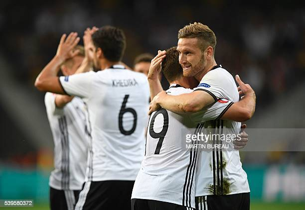 Germany's defender Shkodran Mustafi celebrates with teammates after scoring a goal during the Euro 2016 group C football match between Germany and...