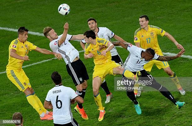 TOPSHOT Germany's defender Shkodran Mustafi heads the ball next to Ukraine's midfielder Taras Stepanenko during the Euro 2016 group C football match...