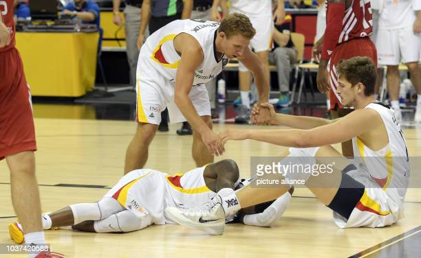 Germany's Dennis Schroeder and Tibor Pleiss fall while teammate Heiko Schaffartzik comes to help during the European Championship basketball game...