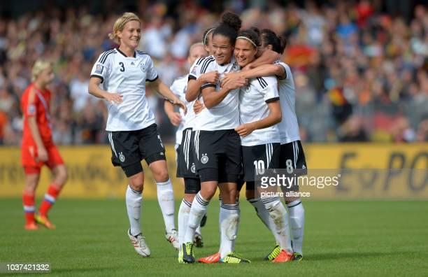 Germany's Dzsenifer Marozsan celebrates her 3-0 goal with team-mates Celia Sasic and Saskia Bartusiak during the qualifying match for the FIFA World...