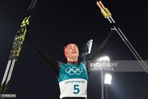 Germany's Eric Frenzel celebrates after winning gold in the nordic combined men's individual normal hill NH/10km cross country final at the Alpensia...