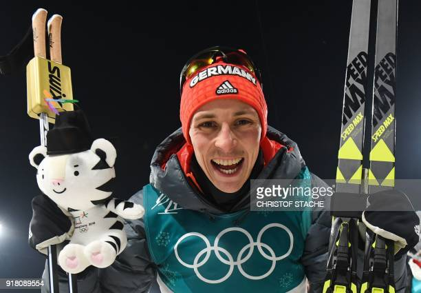 Germany's Eric Frenzel celebrates winning gold during the victory ceremony following the nordic combined men's individual normal hill NH/10km final...