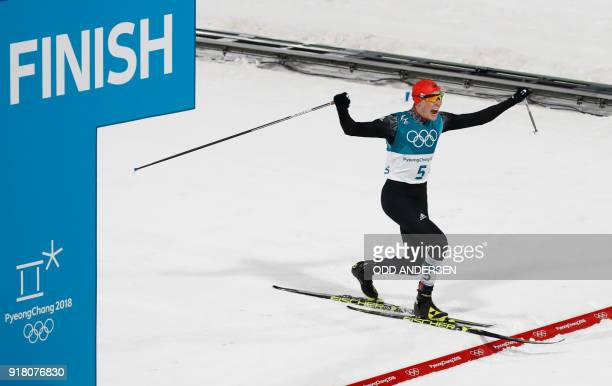 Germany's Eric Frenzel crosses the finish line to win gold in the nordic combined men's individual normal hill NH/10km cross country final at the...