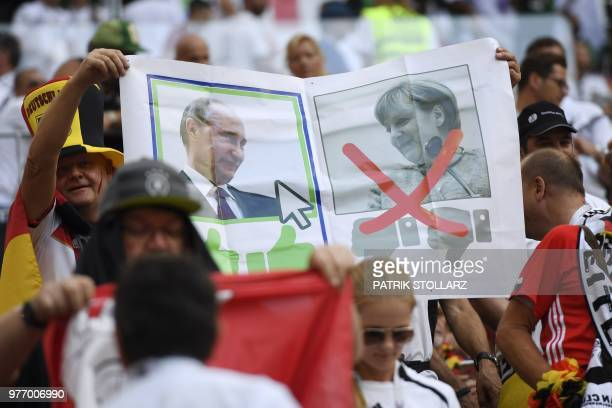 Germany's fans hold a placard picturing Russian President Vladimir Putin and German Chancelor Angela Merkel as they cheer prior to the Russia 2018...
