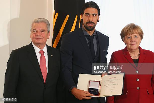 Germanys Federal President Joachim Gauck and German Chancellor Angela Merkel awards Sami Khediraf the German national football team with the...