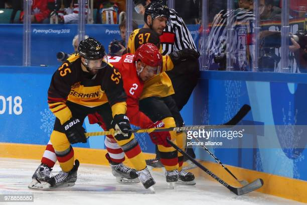 Germany's Felix Schütz Russia's Artjom Sub and Germany's Patrick Reimer battle for the puck during the men's ice hockey gold medal match between...