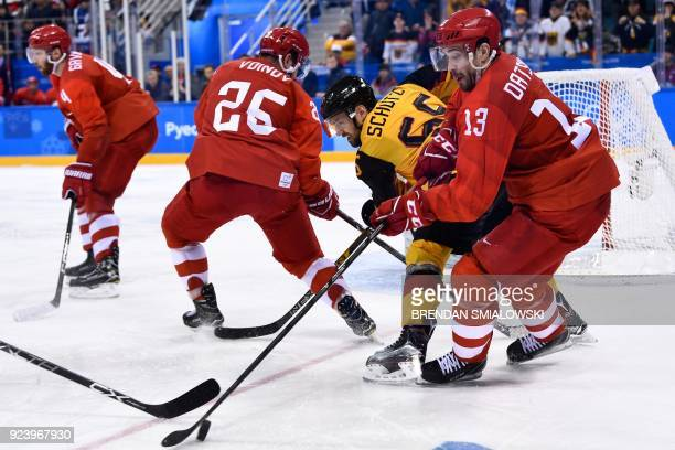 Germany's Felix Schutz and Russia's Pavel Datsyuk fight for the puck in the men's gold medal ice hockey match between the Olympic Athletes from...