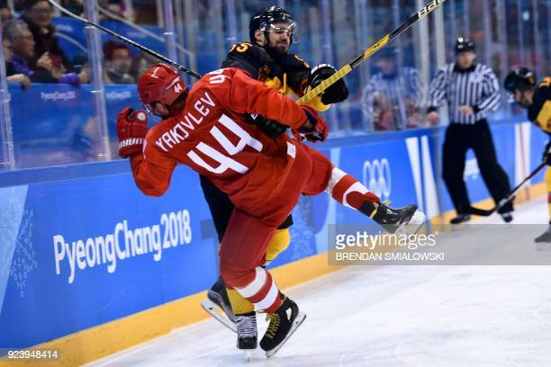 TOPSHOT Germany's Felix Schutz collides with Russia's Yegor Yakovlev in the men's gold medal ice hockey match between the Olympic Athletes from...