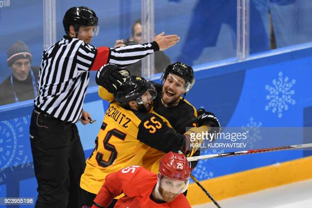 Germany's Felix Schutz is congratulated by teammate Brooks Macek after scoring in the men's gold medal ice hockey match between the Olympic Athletes...