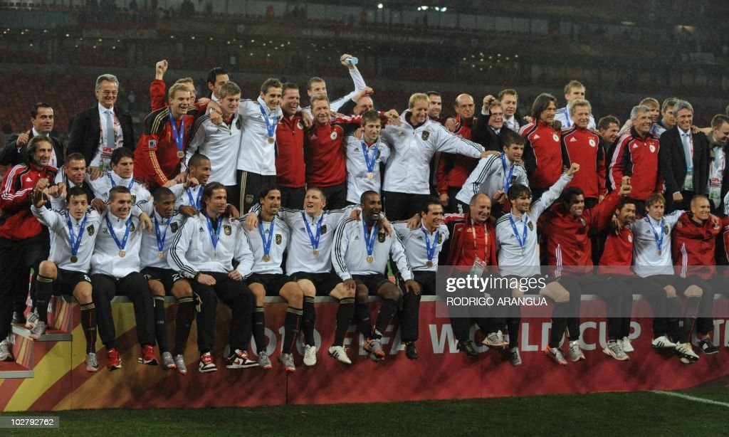 Germany's football squad sit on the podium as they celebrate their third place finish at the end of the 2010 World Cup third place football match between Uruguay and Germany on July 10, 2010 at Nelson Mandela Bay Stadium in Port Elizabeth, South Africa. Germany won the match 3-2. NO
