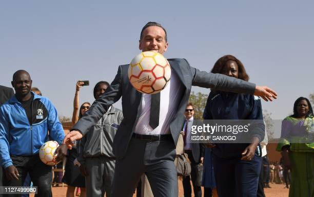 Germany's Foreign Minister Heiko Maas plays football with school children during a visit to Lycee Mixte de Gounghin in Ouagadougou on Febuary 26 as...