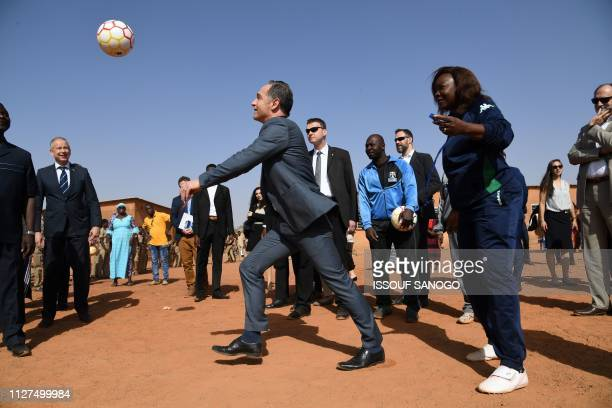 TOPSHOT Germany's Foreign Minister Heiko Maas plays football with school children during a visit to Lycee Mixte de Gounghin in Ouagadougou on...