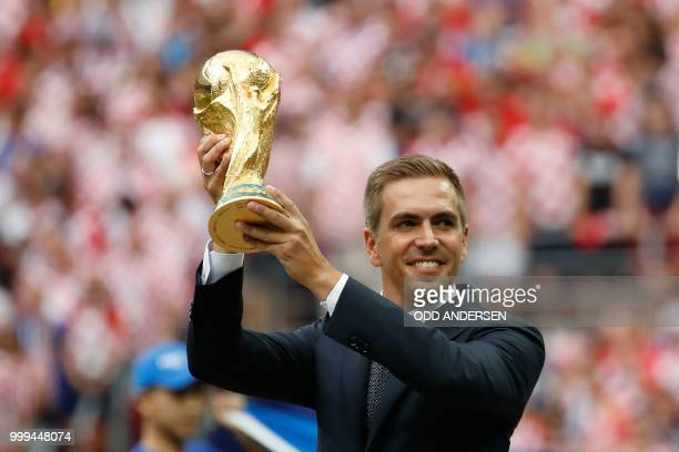 Germany's former captain Philipp Lahm poses with the trophy during the closing ceremony prior to the Russia 2018 World Cup final football match...
