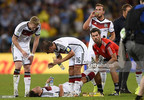 Germany's forward Andre Schuerrle and Germany's defender and captain Philipp Lahm speak with Germany's midfielder Mesut Ozil as hereceives medical...