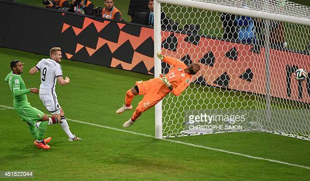 Germany's forward Andre Schuerrle scores past Algeria's goalkeeper Rais Mbohli during the Round of 16 football match between Germany and Algeria at...