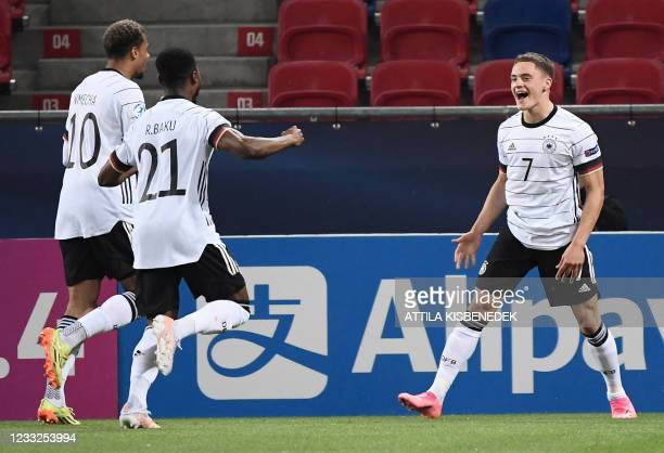 Germany's forward Florian Wirtz celebrates with teammates Germany's forward Lukas Nmecha and Germany's defender Ridle Baku scoring the second goal...