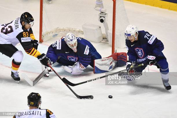 TOPSHOT Germany's forward Leonhard Pfoderl vies with France's defender Thomas Thiry and France's goalkeeper Florian Hardy during the IIHF Men's Ice...
