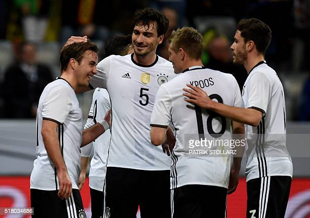 Germany's forward Mario Goetze reacts with teammates after scoring during the friendly football match Germany vs Italy in Munich southern Germany on...