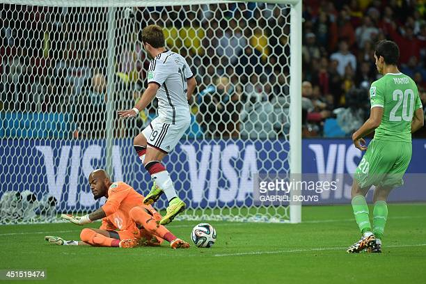 Germany's forward Mario Goetze tries to score a goal as Algeria's goalkeeper Rais Mbohli defends during a Round of 16 football match between Germany...