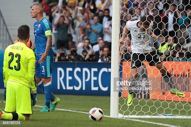 Germany's forward Mario Gomez celebrates next to Slovakia's goalkeeper Matus Kozacik and Slovakia's defender Martin Skrtel after scoring a goal...