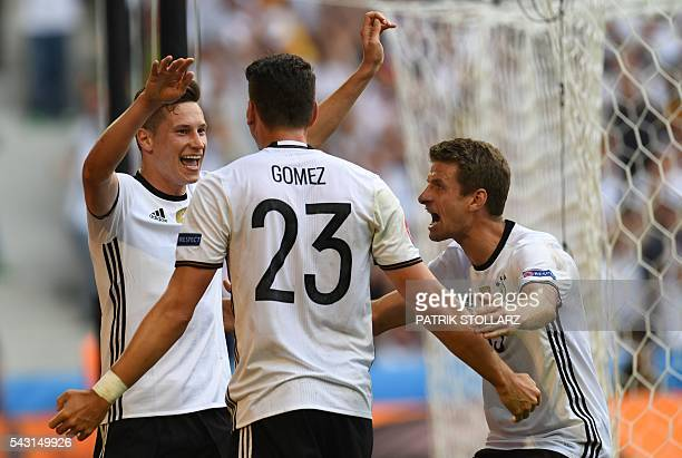 Germany's forward Mario Gomez celebrates with Germany's midfielder Julian Draxler and Germany's midfielder Thomas Mueller after scoring a goal during...
