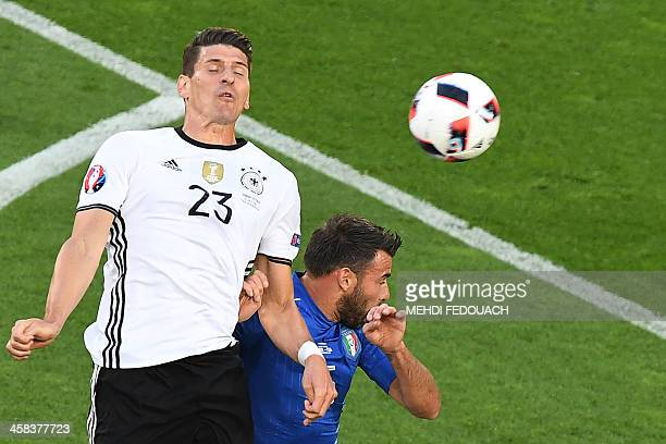 Germany's forward Mario Gomez jumps for the ball with Italy's defender Andrea Barzagli during the Euro 2016 quarterfinal football match between...