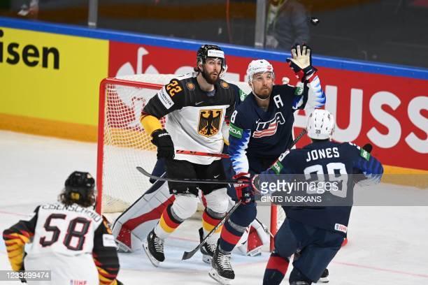 Germany's forward Markus Eisenschmid and US' defender Matt Tennyson eye the puck during the IIHF Men's Ice Hockey World Championships bronze medal...