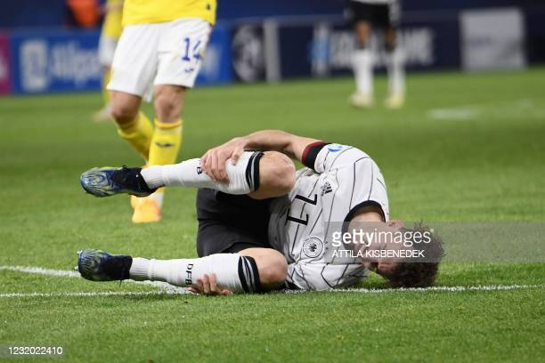 Germany's forward Mergim Berisha lies on the ground during the UEFA Under21 Championship group stage football match Germany v Romania in Budapest, on...