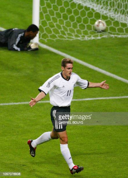 Germany's forward Miroslav Klose celebrates after scoring the first goal against Saudi Arabia as Saudi goalie Mohammed Al Deayea looks at the ball at...
