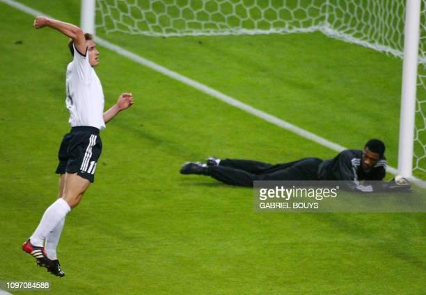 Germany's forward Miroslav Klose celebrates after scoring the first goal against Saudi Arabia as Saudi goalie Mohammed Al Deayea lies on the ground...
